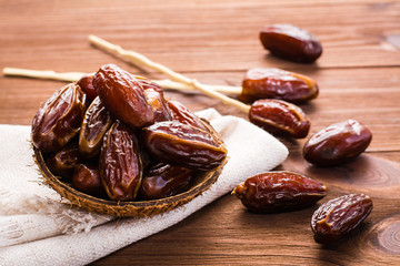 Sweet dried dates fruit in a small bowl on napkin on wooden table