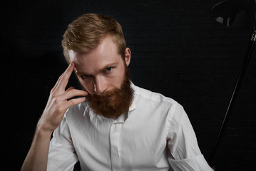 Job, occupation, profession and hobby. Headshot of attractive redhead young Caucasian professional photographer with thick beard dressed in white shirt, looking at camera, sitting in dark studio