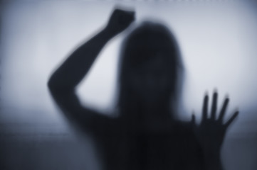 Horror woman behind hitting the matte glass in blurry hand and body figure abstraction