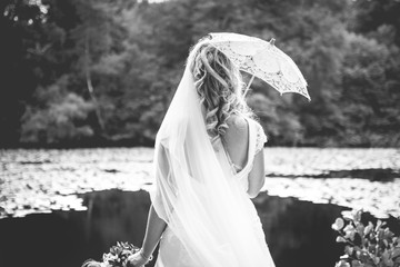 Superb portrait of a bride at the water's edge in the forest on wedding day