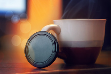 Lens cap, against the background of a cup of tea, the equipment of a photographer