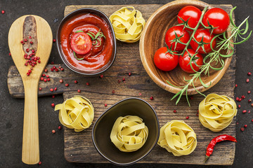 Tomatoes, tomato sauce, pasta, rosemary, red pepper for cooking dishes on a dark background. Top View.