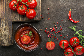 Dark ceramic bowl with tomato sauce, fresh vegetables, herbs, pepper on a dark background. Top View.