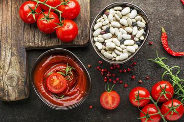 Dark ceramic bowl with tomato sauce, Assorted legumes, fresh vegetables, herbs, pepper on a dark background. Top View
