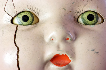 Creepy old doll head with spooky green eyes.