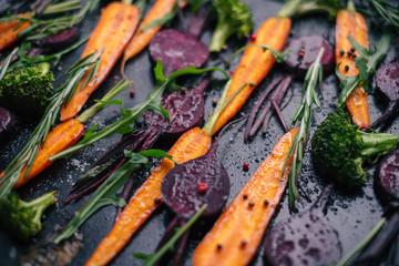 Fresh vegetables for roasting on rustic dark background