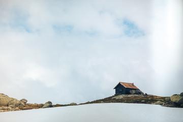 Śnieżny góra krajobraz z małym domem. Narodowa Trasa Turystyczna. Rallarvegen, Norwegia. - 165336390
