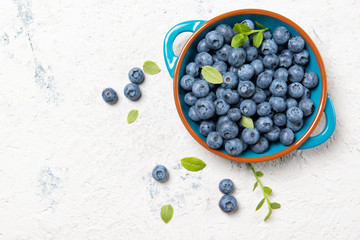 Fresh ripe blueberries with leaves in a bowl on a stone table, top view with copy space