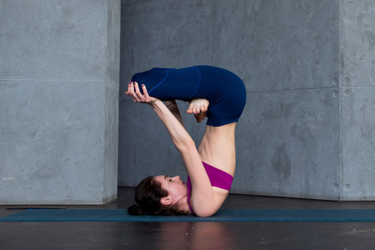 Advanced young yogini practicing Hatha yoga standing in inverted lotus pose, padmasana, on mat