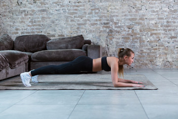 Slim young brunette wearing black gym clothing doing abdominal bridge or front plank exercise in loft apartment.