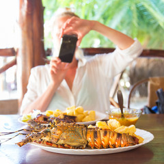 Foodie blogger on tropical vacations using mobile phone to take photo of a plate of grilled lobster served with potatoes and coconut sauce.
