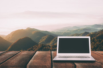 Laptop with blank screen on wooden table with forest in mountain
