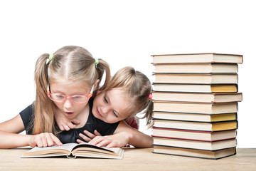 Two girls sitting at a desk with a stack of books surprised studying an open book isolated on a white background