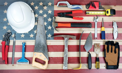 Labor Day holiday background with USA rustic wooden flag and many worker tools