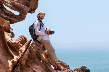 Traveller with camera sits on the edge of a cliff.