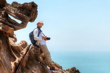 Photographer sits on a rock while traveling, Hormuz Island, Iran.