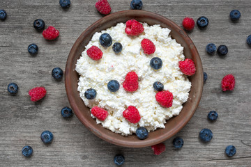 cottage cheese with fresh raspberries and blueberries in a bowl for healthy breakfast