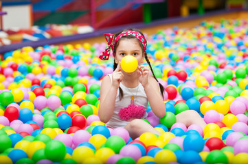 Little girl playing with colorful balls