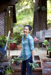Woman smiling holding plants in her yard