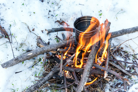 Survival in the winter - boiling water for tea over small campfire