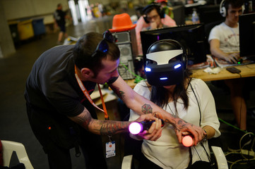 A man gives instructions to a woman wearing a virtual reality headset at the 25th Euskal Encounter, a four-day party during which over 5,000 computers are linked via local and high speed internet connections, in the Bilbao Exhibition Centre, Barakaldo