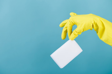 hand  in yellow glove holding sponge on blue background. cleaning