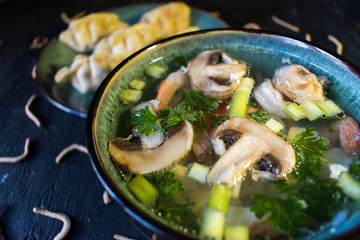 Shrimp and vegetables in clear broth soup closeup