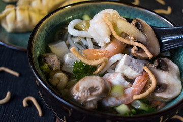 Shrimp and vegetables in clear broth soup closeup with spoon