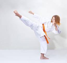 A circular kick is training by a girl in karategi