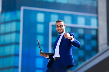 Successful young businessman with laptop expressing positivity while standing outdoors with office building in the background.