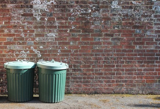 trash can trash-can garbage stock rubbish bin dustbin can background outside against brick wall with copy space stock, photo, photograph, image, picture
