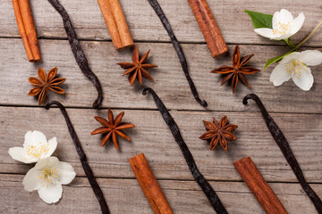 Vanilla sticks and cinnamon with anise and flower on a old wooden background