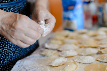 Closeup view of making traditional dumplings on kitchen table background