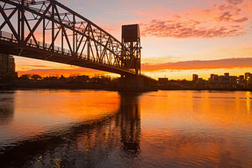 Scarlet sunrise with Roosevelt Island Bridge across the East Channel in New York, USA. Bridge engineering design highlighted by pastel colors of the sky at sunrise.