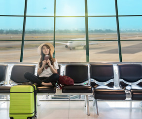 Happy Asian woman traveler holding the passport with suitcases and waiting for airplane arrive in modern an airport, travel and transportation with technology concept.