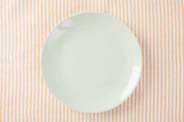 Top view of empty green plate put on cloth table with space for copy.
