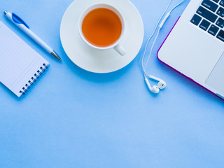 Top view of feminine desk workspace with office accessories including laptop, note book, white pen and coffee on blue background.