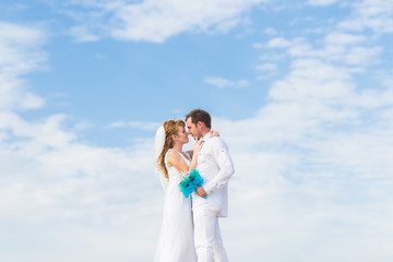 Elegant stylish happy bride and gorgeous groom on the background of the blue sky