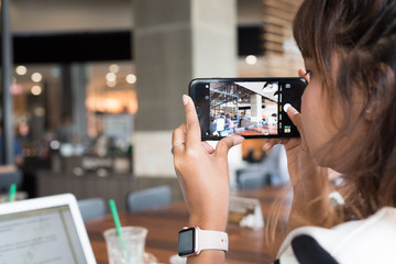 Asian woman using smartphone take a photo in coffee shop. Coffee shop is a most popular place to check in and take a photo to social networks
