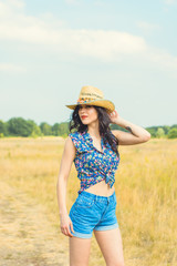 Beautiful hot sexy woman with bright make up wearing in american country style, straw hat and jeans shorts on a gold field background sky
