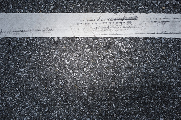 A dark asphalt pavement texture with aged and weathered horizontal traffic sign painted with white color