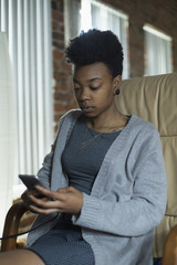 Young woman using mobile phone sitting on armchair at home