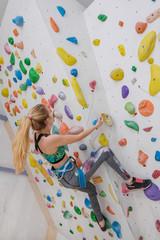 Woman climbing on climbing wall. Teenage rock climber.