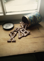 High angle view of alphabet cookies spilling from can on table by window