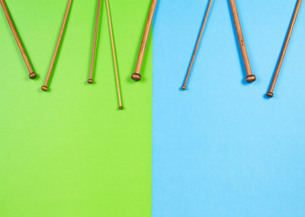 Wooden knitting needles frame on colorful background