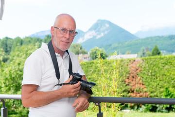 mature man with dslr camera, outdoors
