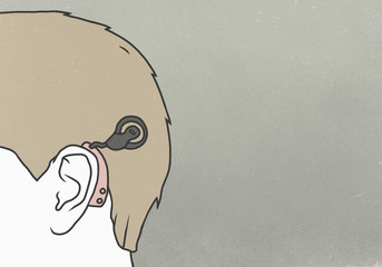 Cropped image of man wearing hearing aid against gray background
