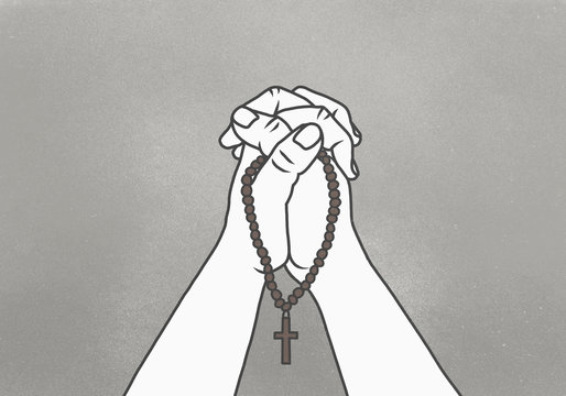 Cropped image of clasped hands holding rosary beads against gray background