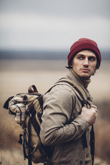 Thoughtful hiker carrying backpack and looking away while standing outdoors