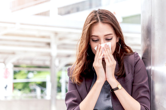 Sick business woman with sneezing in tissue
